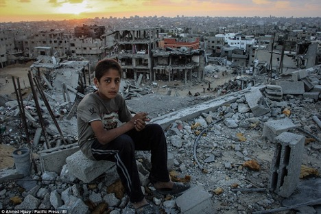 A child sitting amidst rubble in Gaza